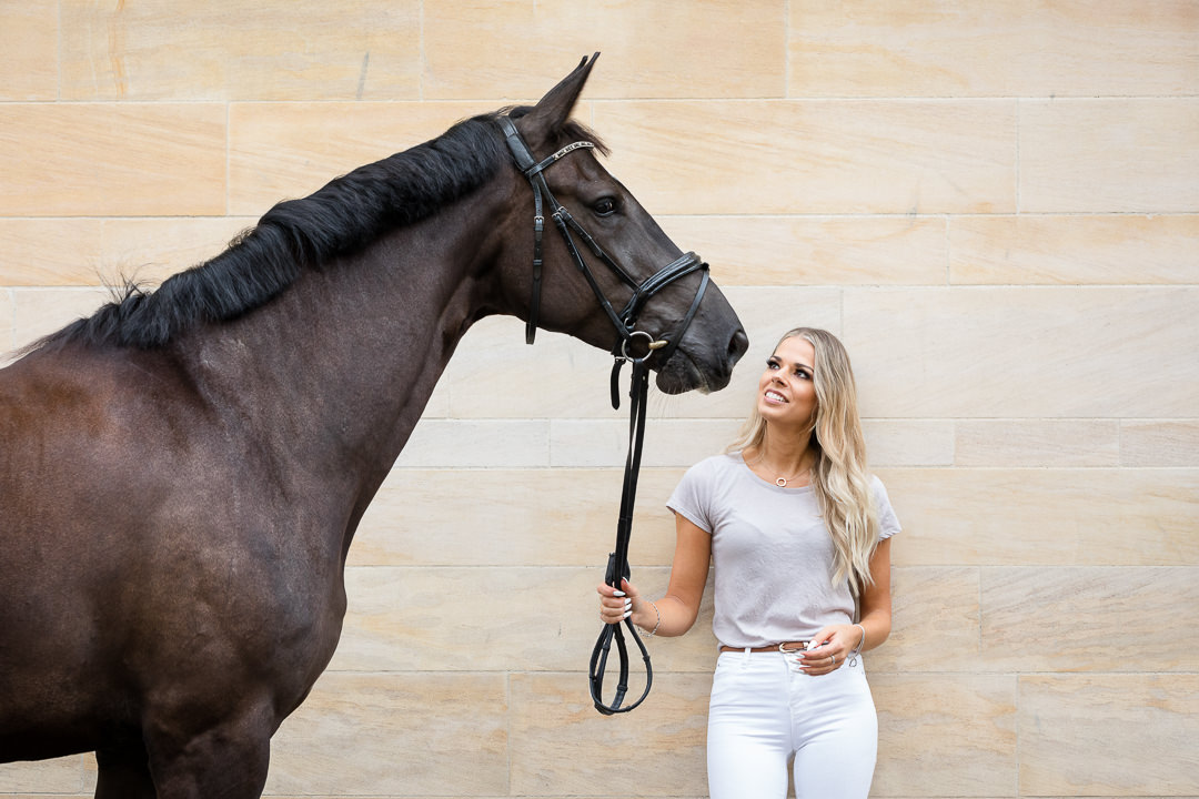 lady looking up at her dressage horse against a stone wall